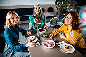 Cheerful ladies sitting at the table in cafe