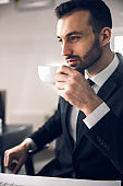 Caucasian relaxed man drinking coffee at workplace in office