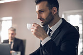 Caucasian man enjoying coffee at workplace in office