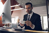 Caucasian attractive man drinking coffee at workplace in office