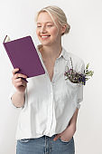 Cheerful young woman reading book and smiling
