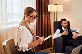Serious man and woman working with gadgets in hotel room