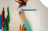 Kid hand drawing on piece of paper