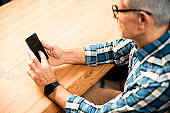 Mature man using mobile phone at the table indoors