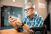 Mature man holding smartphone while looking at screen