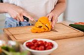 Woman chopping orange pepper