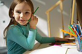 Cute little girl drawing with colored pencils at home