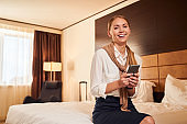 Cheerful young elegant woman with smartphone in hotel room