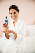 Happy woman with serum for face care