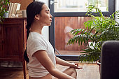 Profile portrait of a young serious woman doing meditative practices