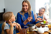 Happy mother enjoying breakfast with adorable kids