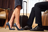 Elegant man and woman with suitcase at hotel