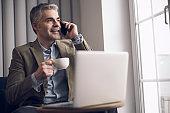 Caucasian mature businessman talking on cellphone during coffee break