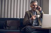 Caucasian smiling businessman talking on cellphone during coffee break
