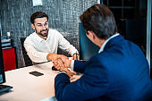 Smiling office worker shaking his customers hand