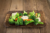 Stir fried broccoli in oyster sauce on wood background.