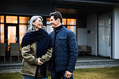 Smiling mature husband standing with his wife in the backyard of the house