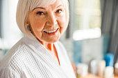 Joyful elderly woman looking at camera and smiling