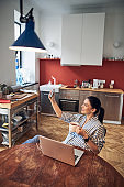 Charming lady drinking tea near laptop at home