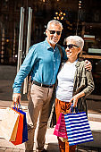 Cheerful senior couple standing on the street after shopping