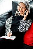 Pleased businesswoman during phone conversation stock photo