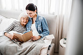 Joyful old woman reading book with adult granddaughter