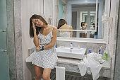 Woman having headache in bathroom
