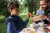 Joyful father having breakfast with son outdoors