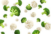 Falling cauliflower and broccoli, isolated on white background, selective focus