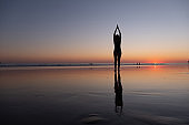 A young woman with long hair in a bathing suit is doing yoga on the seashore and you can see the reflection of her slender body on the wet sand in the sunset rays