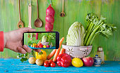 shooting with smartphone organic food ingredients,vegetables, kitchen utensils, healthy eating concept,  uploading to social media