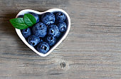 Freshly picked organic blueberries in a white heart shaped bowl on wooden background.Blueberry. Bilberries.Healthy eating,vegan food or diet concept with copy space.