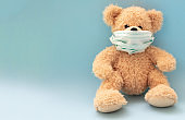 Coronavirus and pollution protection concept. Teddy bear with protective face mask on blue background