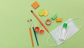 Medical protective mask, hand sanitizer gel and school supplies on pastel green color background, top view, Back to school, coronavirus days.