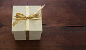 Beige closed gift box with gold color ribbon on wooden table