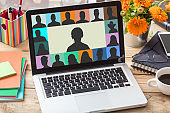 Group of people on a laptop screen on office desk background. Video conference concept