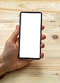 Man holding a smart phone with blank screen, wooden background