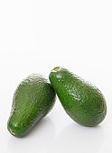 Avocados isolated on white background, whole unpeeled fresh vegetables, healthy food