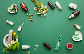 Homeopathy, globules and herbs on green background