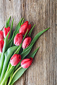 Red tulips bouquet isolated on wooden background