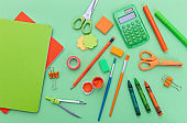 School supplies on green color background, top view