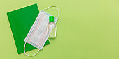 Coronavirus spread prevention measure at school. Surgical mask, alcohol disinfection gel and notebook on green background.