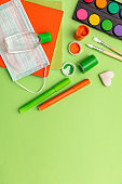 Coronavirus spread prevention measure at school. Surgical mask, alcohol disinfection gel and stationery on pastel green background,