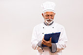 Senior chef holding cookbook