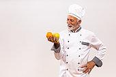 Senior chef holding  fruit and thinking
