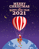 Santa Claus Van with text Merry Chrismas and Happy New Year 2021 flying in flying in a hot air balloon delivering shipping gifts on night winter Earth