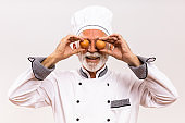 Senior chef covering eyes with eggs
