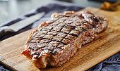 grilled new york strip steak resting on wooden cutting board
