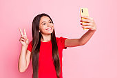 Photo of lovely sweet little lady long hairstyle raise hand hold telephone show v-sign take selfie video message look screen wear casual red t-shirt isolated pink color background