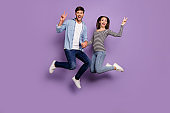 Full length photo of two people couple funny guy lady jumping high holding hands showing v-sign symbols wear stylish casual clothes isolated pastel purple color background